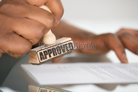 persons hand stamping on contract form