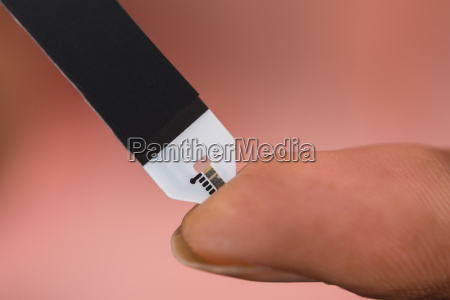 persons hand checking blood sugar level