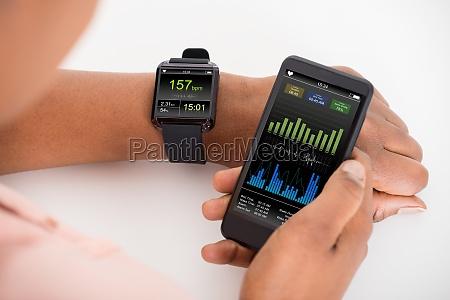 hand mit mobile und smartwatch zeigen