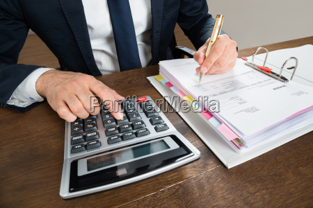 businessman using calculator while checking invoice