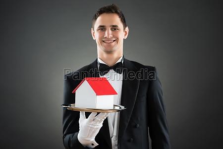 happy waiter holding house model in