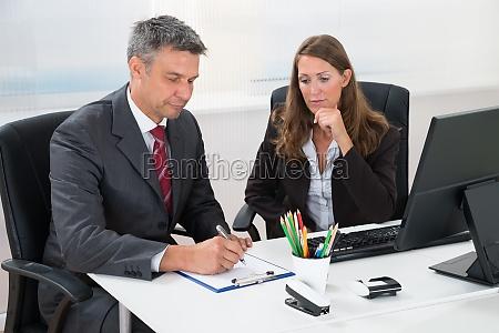 schreiben geschaeftsmann auf zwischenablage mit assistent