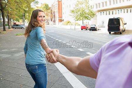 woman pulling her husband