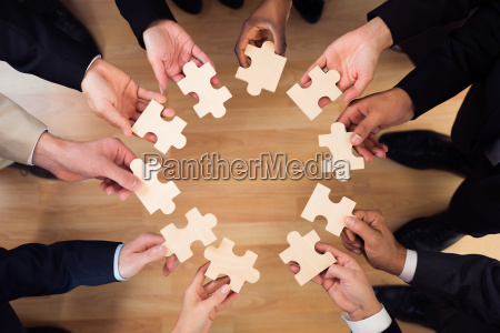business people joining puzzle pieces in