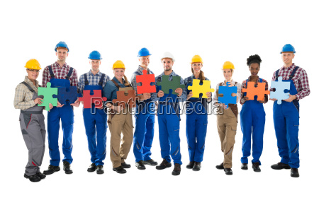 confident construction workers holding jigsaw pieces