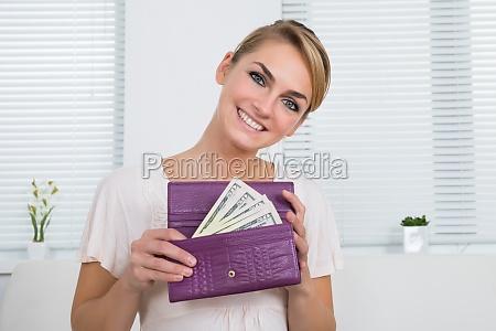 glueckliche frau zeigt geld im geldbeutel