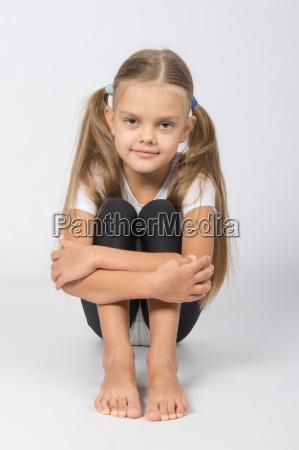 girl gymnast sitting on the floor