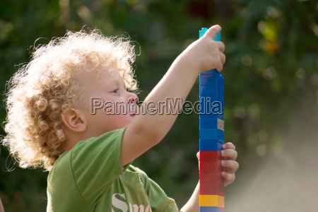 little blond boy playing with blocks