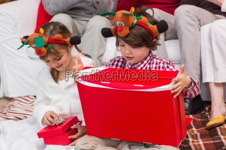 festive sibling opening a gift