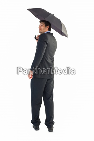 businessman looking up while holding black