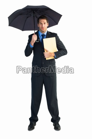 businessman standing under umbrella while holding