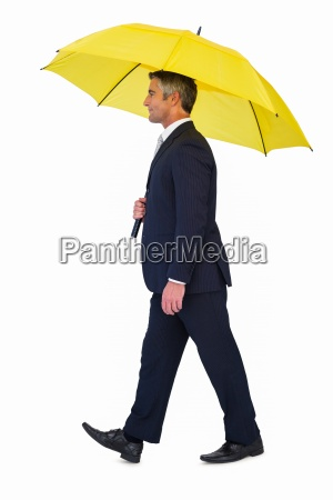 businessman walking and holding yellow umbrella