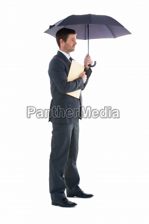 businessman holding a file under umbrella