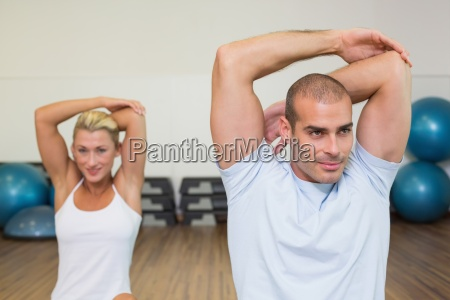 couple stretching hands behind back in