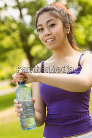 healthy woman holding water bottle in