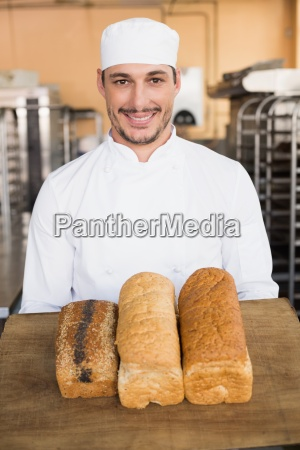 smiling baker showing loaves of bread