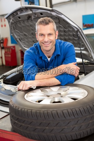 mechanic smiling at the camera with