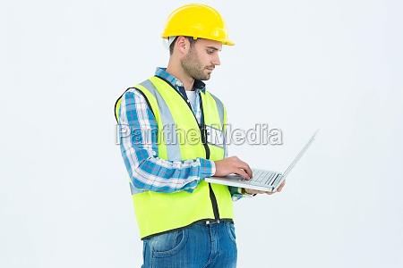 reparaturmann in reflektierter arbeitskleidung mit laptop