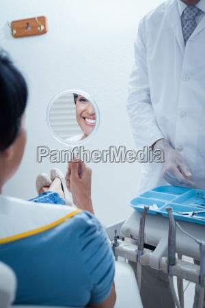 smiling young woman looking at mirror