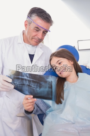 pediatric dentist explaining to young patient