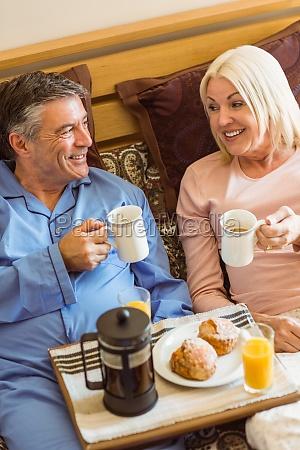 happy mature couple having breakfast in