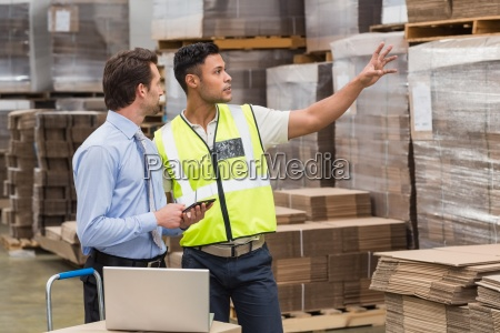 warehouse worker showing something to his