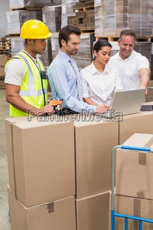 warehouse managers and worker looking at