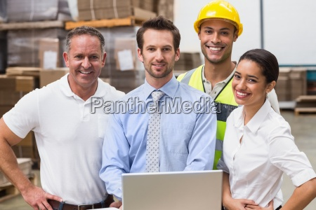 warehouse managers and worker smiling at