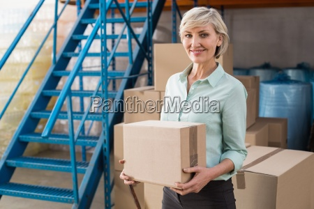 smiling warehouse manager holding cardboard box