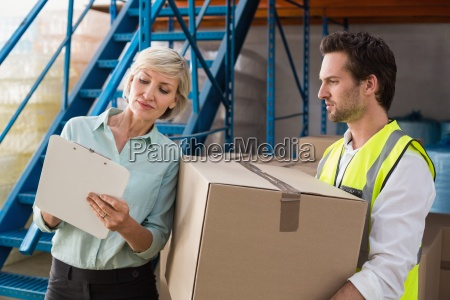 warehouse manager and worker looking at