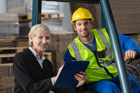 forklift driver and manager smiling at