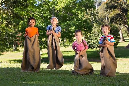kinder die ein sackhuepfen im park