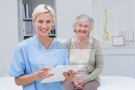 nurse holding clipboard while female patient