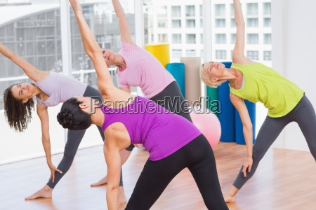 female instructor guiding friends in stretching