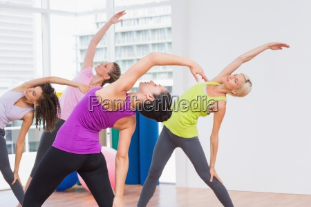 instructor and female friends doing stretching