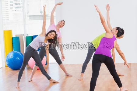 trainer and female friends doing stretching
