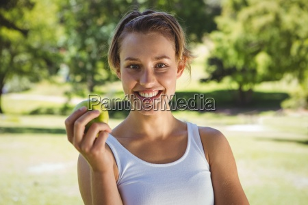 fit woman holding green apple