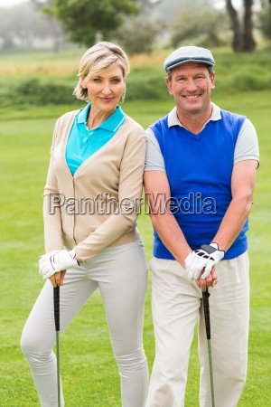 golfing couple smiling at camera on