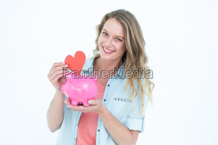 smiling woman holding piggy bank and