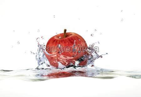 roter apfel spritzer ins wasser nahaufnahme