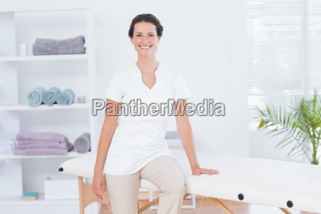 smiling doctor looking at camera sitting