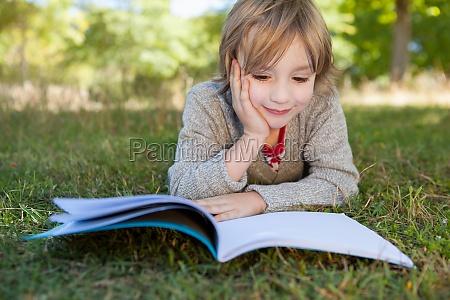cute little boy reading in park