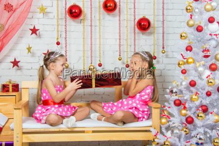 sister gives girl a gift girl