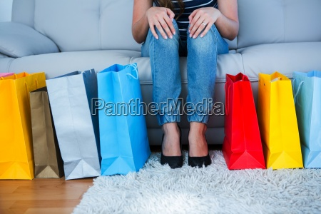 woman sitting on couch with shopping