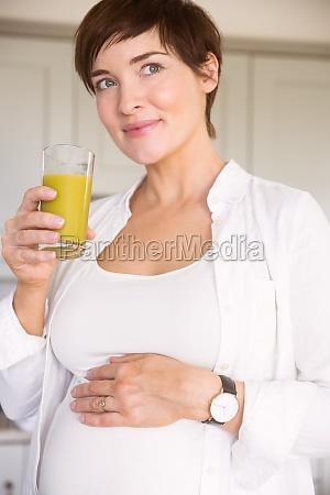 pregnant woman drinking glass of orange