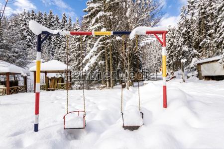 kinderspielplatz unter schnee im winter