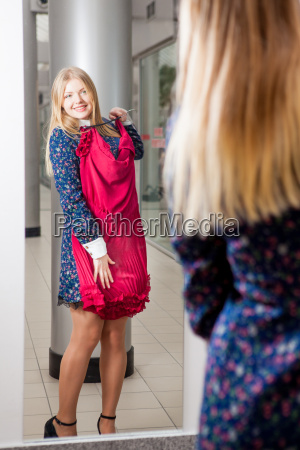 woman trying red dress shopping for