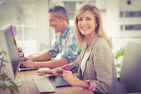 smiling casual designer vor ihrem arbeitskollegen