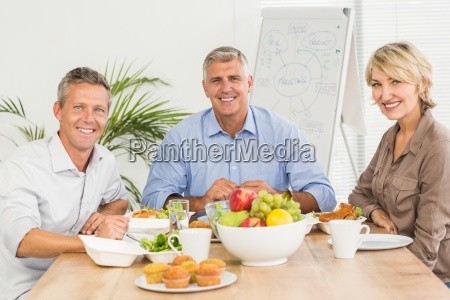 smiling business colleagues having lunch together