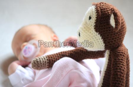schlafende neugeborene wird von gehaekeltem affen